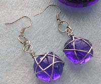 Fashion earring with wired-in star transparent dark blue glass bead suspended on bottom